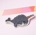 Narwhal brooch in brick stitch weaving on glittery fabric